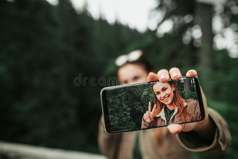 Young lady holding smartphone with her selfie on display. Look at me. Close up of mobile phone with photo of smiling girl in female hand. Woman and green forest stock photos