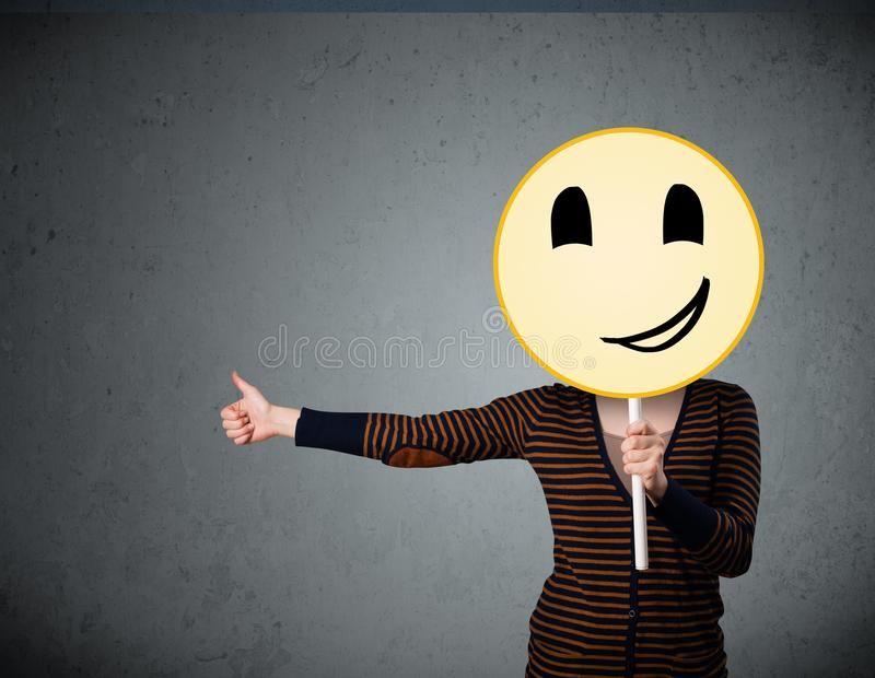 Young woman holding a smiley face emoticon. Young lady holding a yellow smiley face emoticon in front of her head royalty free stock photo