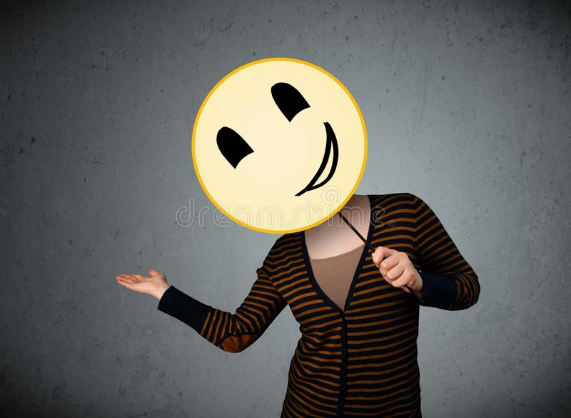 Young woman holding a smiley face emoticon. Young lady holding a yellow smiley face emoticon in front of her head royalty free stock images