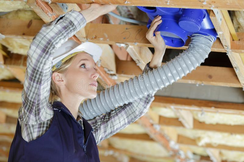 Young lady installing air conditioning unit. Young lady installing an air conditioning unit royalty free stock photos