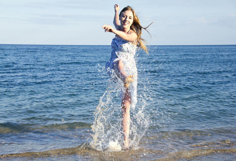 Young lady jumping with splash in the sea royalty free stock image