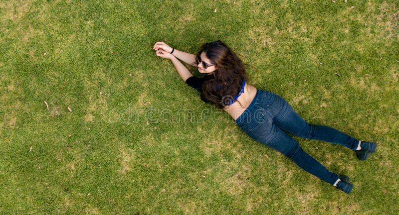 Young lady laying in the grass stock photo