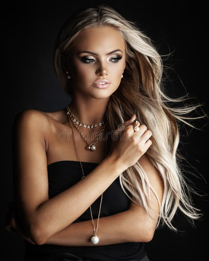 Young lady with luxury jewelry in modern interior stock images