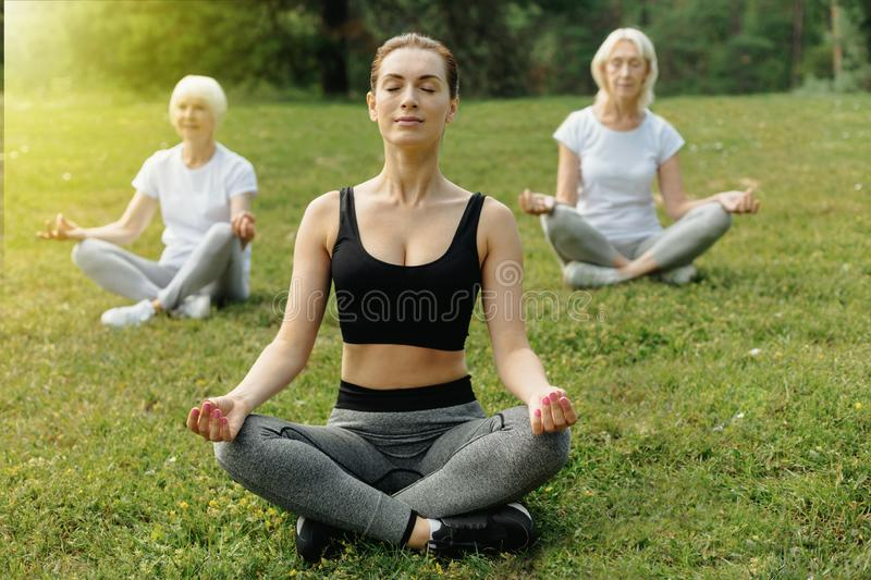Young lady mediating during yoga practice with older people stock photography