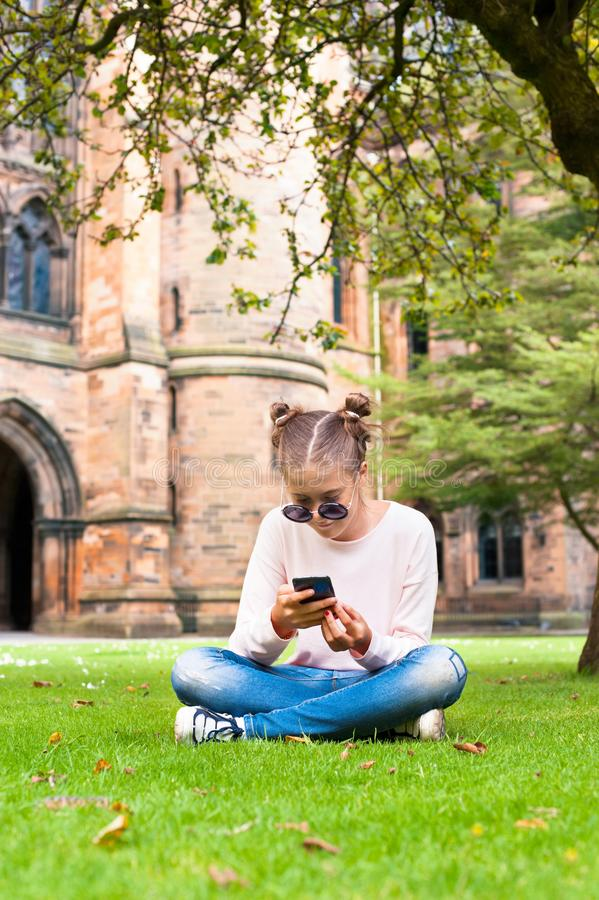 Young lady with mobile phone sitting in Glasgow University garden. royalty free stock image