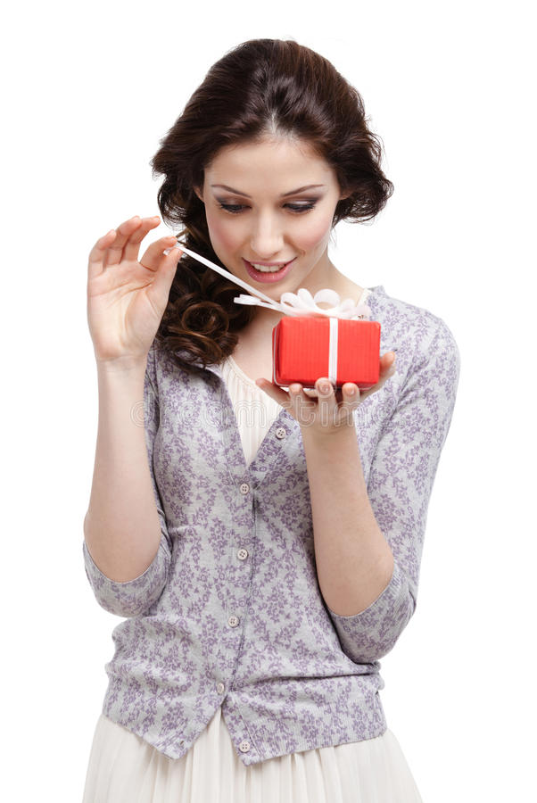 Young lady opens her present. Wrapped in red paper, isolated on white royalty free stock photography
