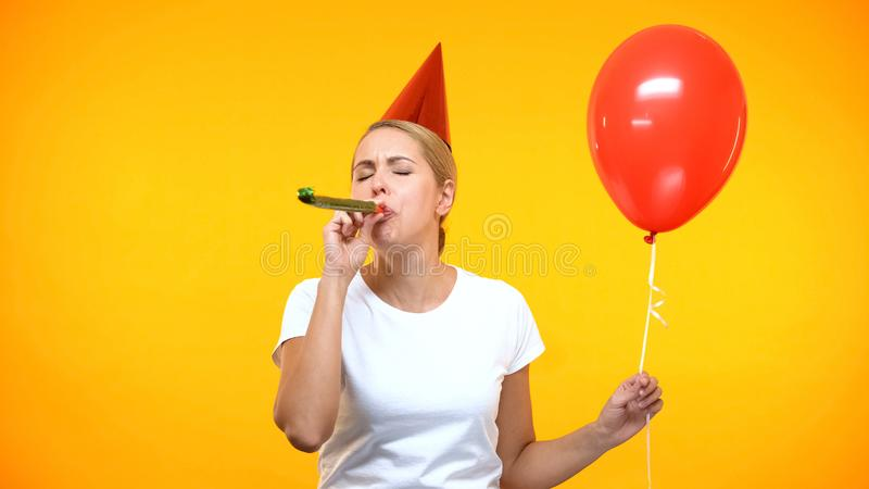 Young lady in party hat blowing horn, holding red balloon, birthday celebration. Stock photo royalty free stock images
