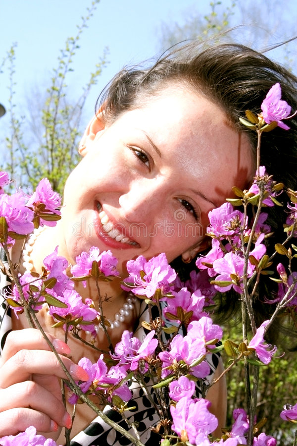 Young lady in pink rhododendrons royalty free stock photos