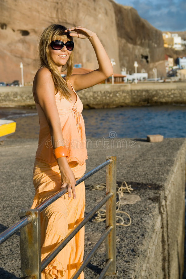 Young lady in a port looking to the horizon royalty free stock image