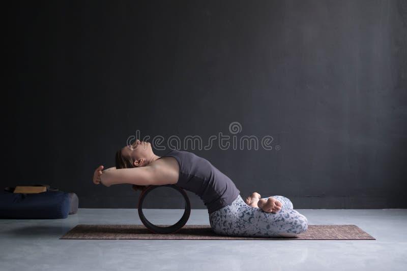 Woman practicing yoga in lotus fish posture Matsyasana stock images