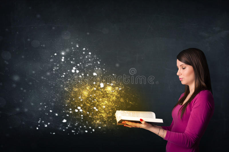 Young lady reading a magical book. In front of a blackboard stock photos