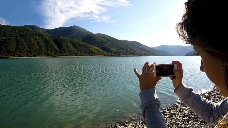 Young lady recording video of sunlit mountain scenery and river using smartphone stock photography