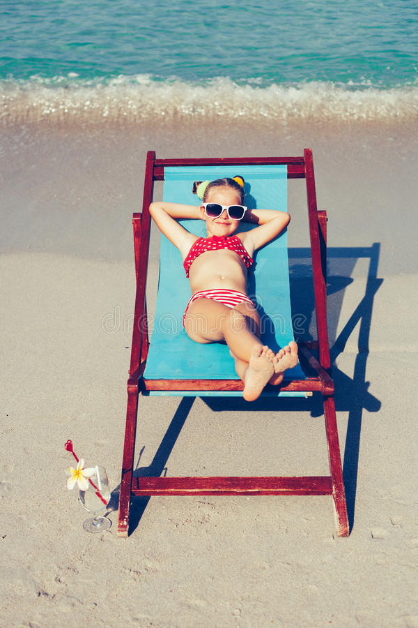 Young lady relaxing in a chair on a tropical beach with white sand royalty free stock photo