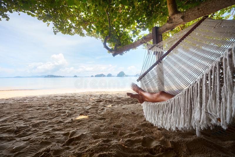 Young lady relaxing in the hammock. On the sandy beach with tropical islands on the horizon stock image