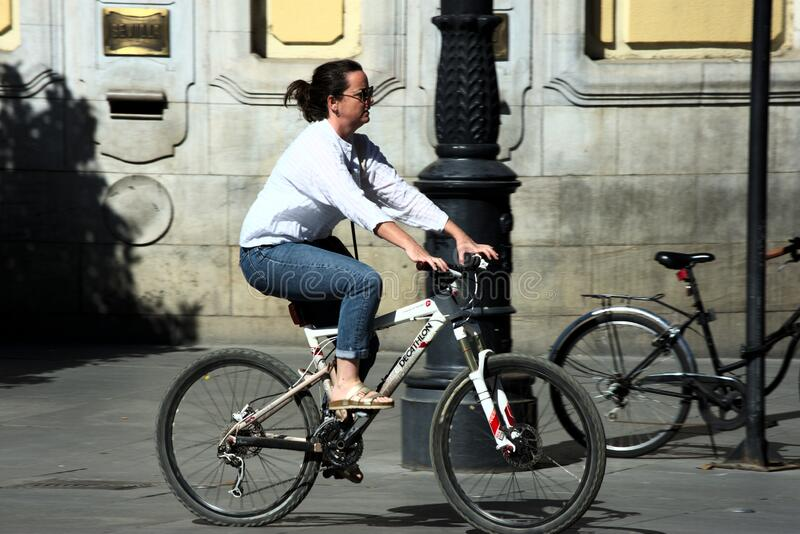 Young lady riding a bicycle in Seville stock image