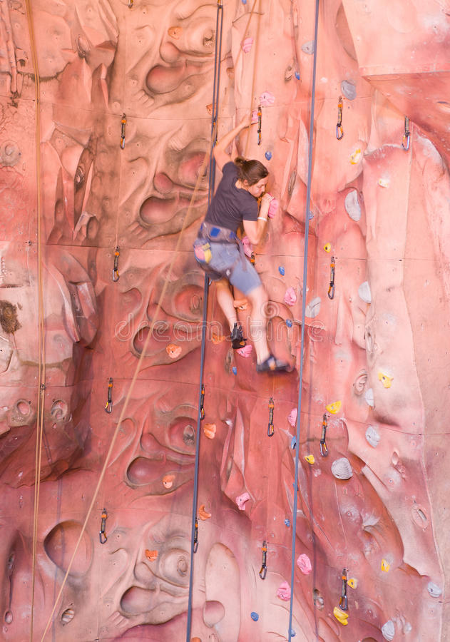 Young lady rock climbing royalty free stock image
