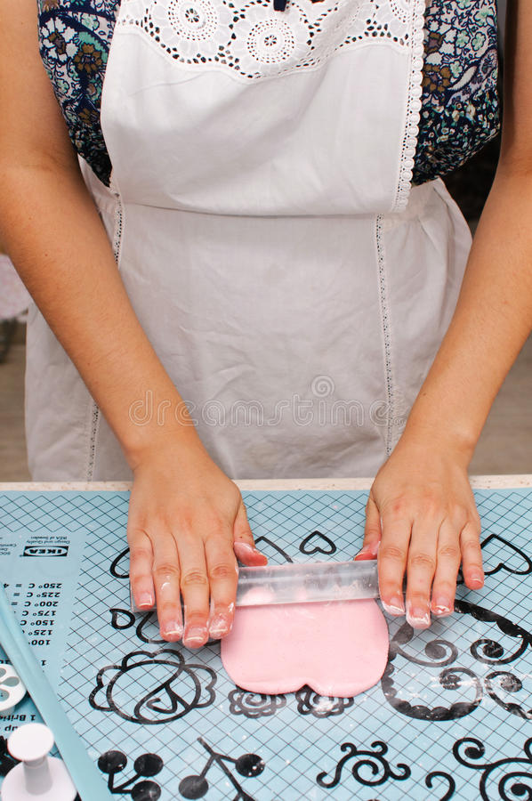 Young lady rolling fondant royalty free stock photography