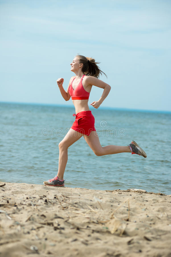 Young lady running at the sunny summer sand beach. Workout. Jog stock photo