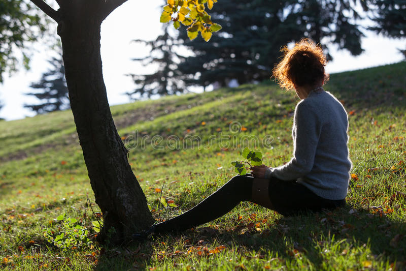 Young lady seats on the grass royalty free stock photo