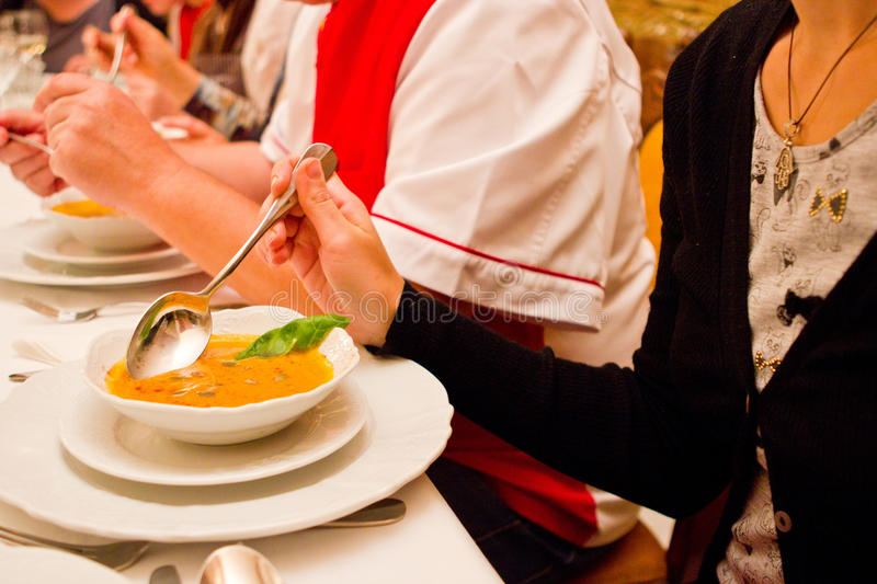 Young lady serving soup royalty free stock image