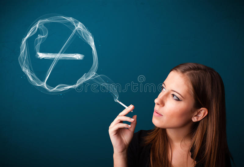 Young lady smoking unhealthy cigarette with no smoking sign. Pretty young lady smoking unheathy cigarette with no smoking sign royalty free stock photography