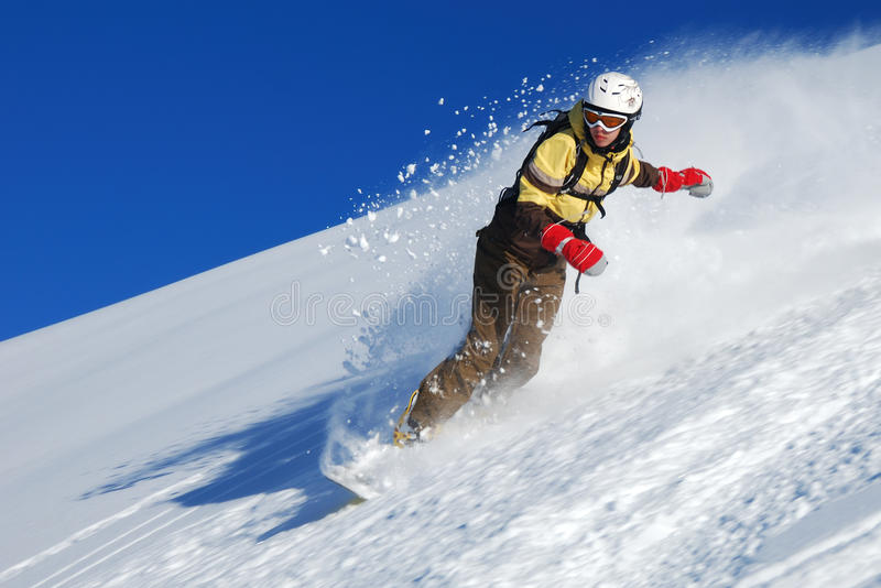 Young lady snowboarder riding stock images