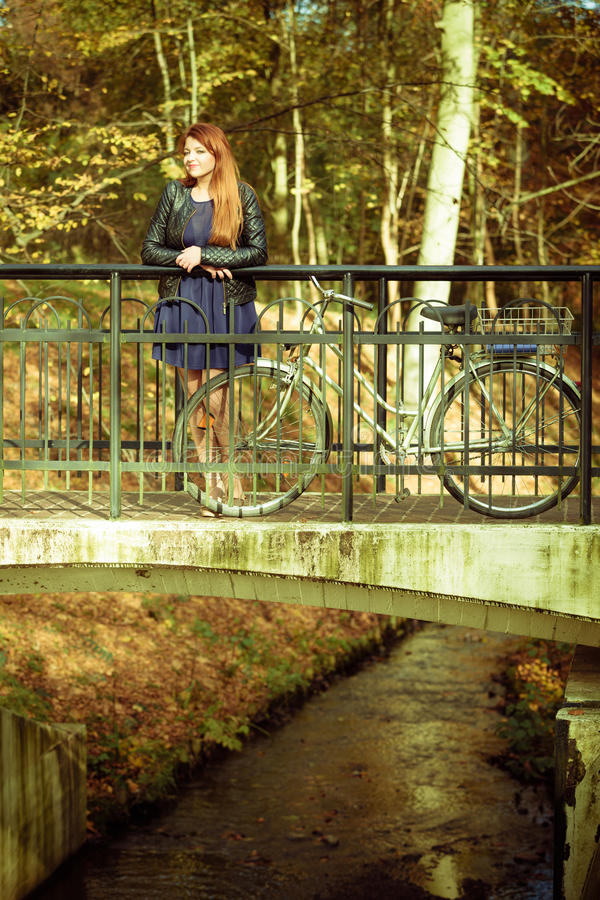 Download Young Lady Is Standing On The Bidge With Her Bike. Stock Image - Image of park, time: 83711345