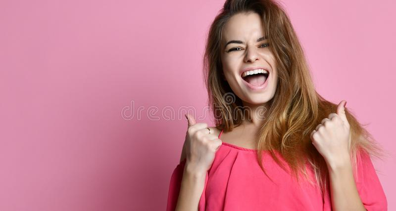Young lady standing isolated over pink background make winner gesture. royalty free stock photo