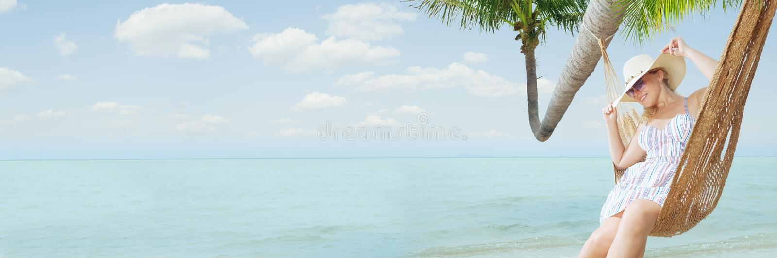 young lady swinging  in hummock on tropical beach stock photography