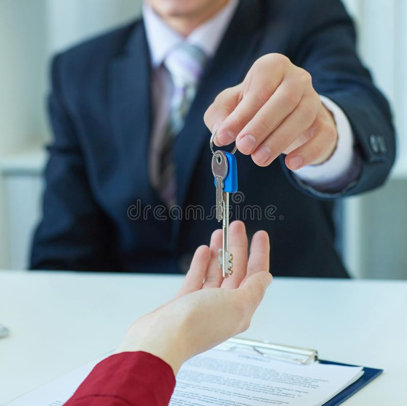 Young lady taking keys from male real estate agent during meeting after signing rental lease contract or sale purchase royalty free stock photo