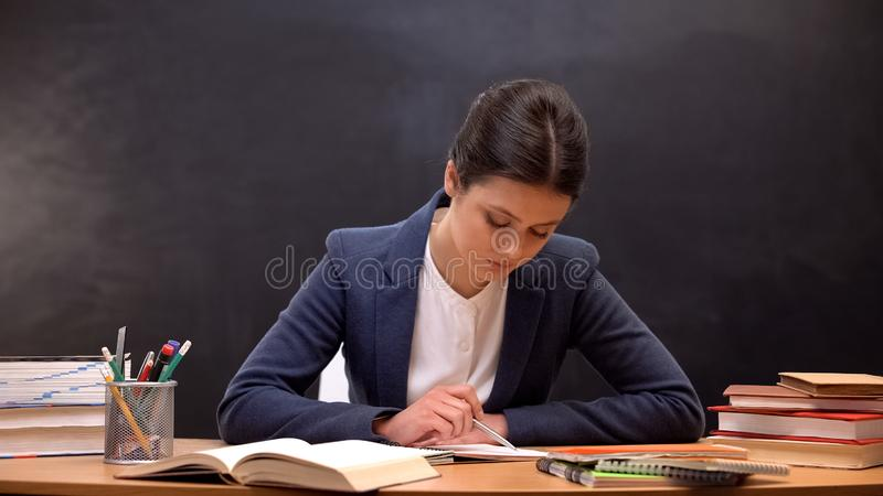 Young lady teacher checking schoolchildrens assignments, occupation, paperwork stock photos