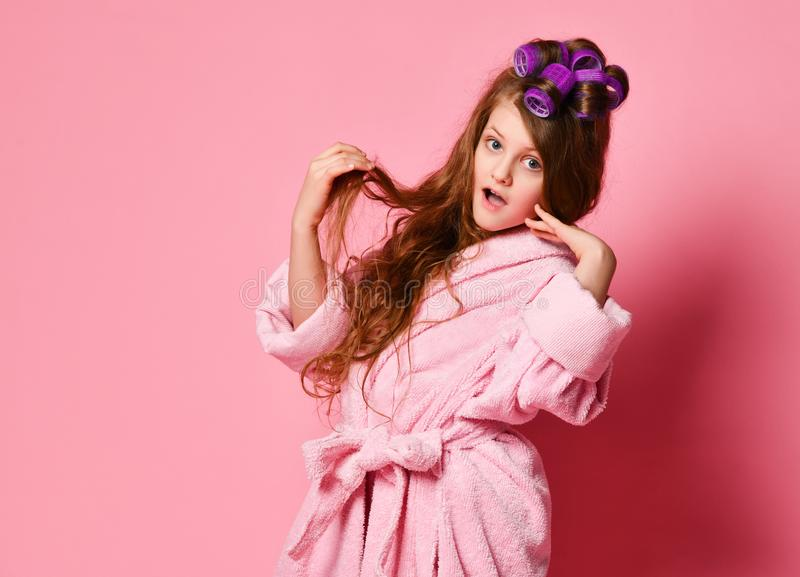 Young lady or teen girl in spa salon is surprised or frightened with her hair style condition. Acts like picky insta-model. Beauty concept on pink background stock photos