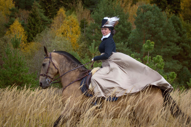 Young lady in 19th century dress riding a akhal teke horse. Young pretty lady galopping on a akhal teke horse. Nineteenth century dress. Autumn hunting with stock images