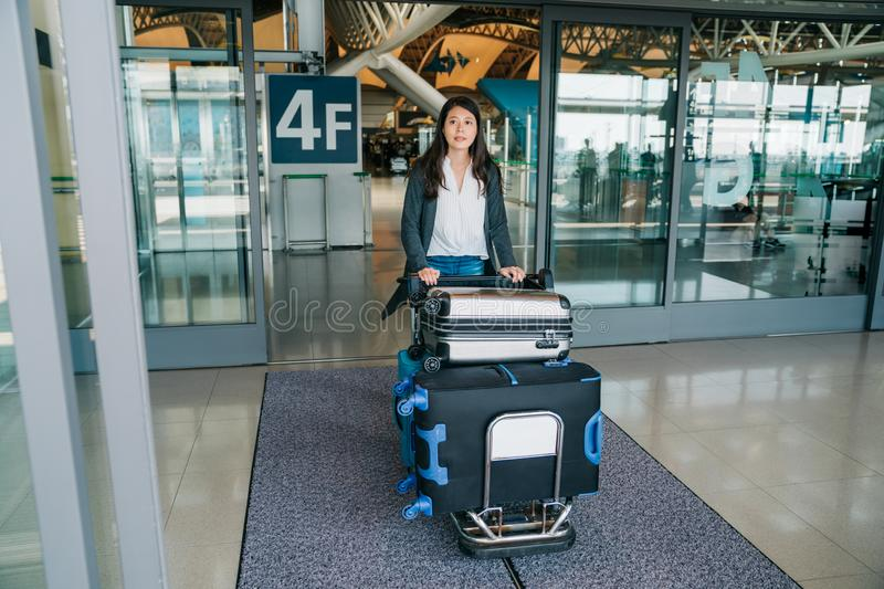 Young lady traveler rolling the cart arrive. Elegant tourist pushing luggage trolley walking out from airport hall. young lady traveler rolling the cart arrive royalty free stock photos