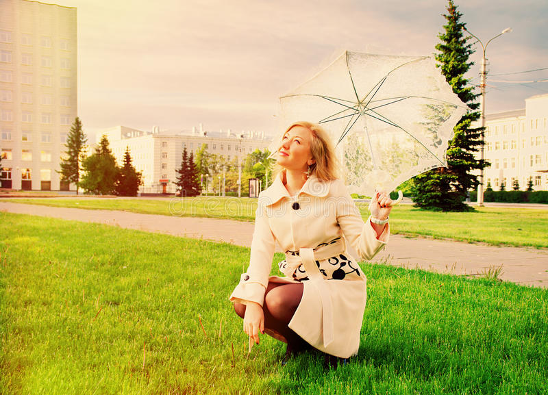 Young lady with umbrella. Beautiful young lady with umbrella in city without people royalty free stock photos