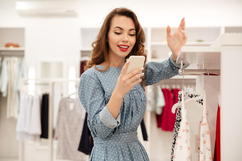 Young lady using smartphone and leaning on shelf. In shop stock image