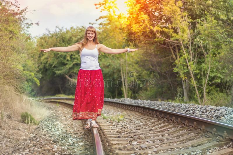 Young lady walking on railway tracks royalty free stock photography