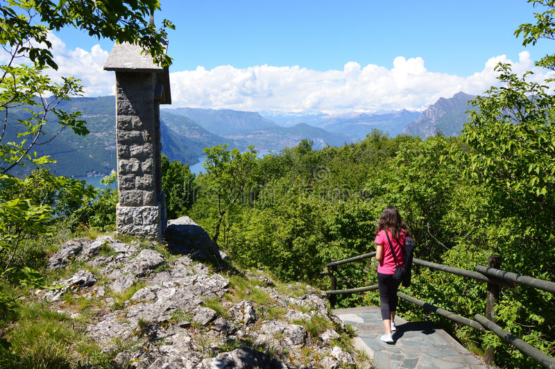 Young lady walks a mountain path to Monte Isola, mountain road landscape, Lombardy, Italy royalty free stock image