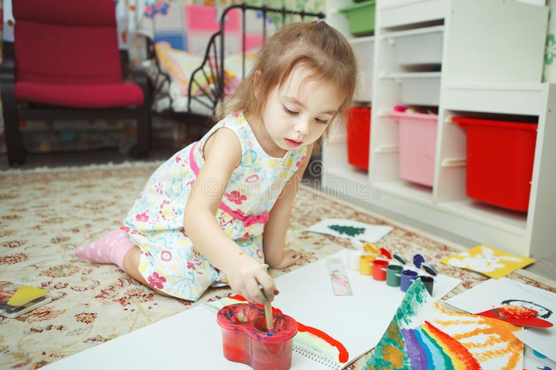 Young lady wearing dress and drawing picture with gouache royalty free stock photos