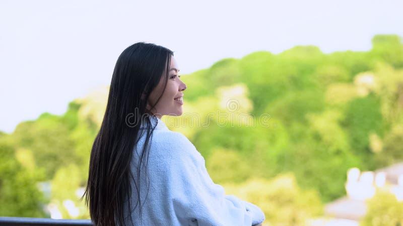 Young lady wearing white bathrobe enjoying morning outdoors on hotel terrace royalty free stock photos