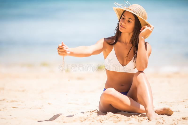The young latin beautiful girl playing with sand on a sea beach royalty free stock photo