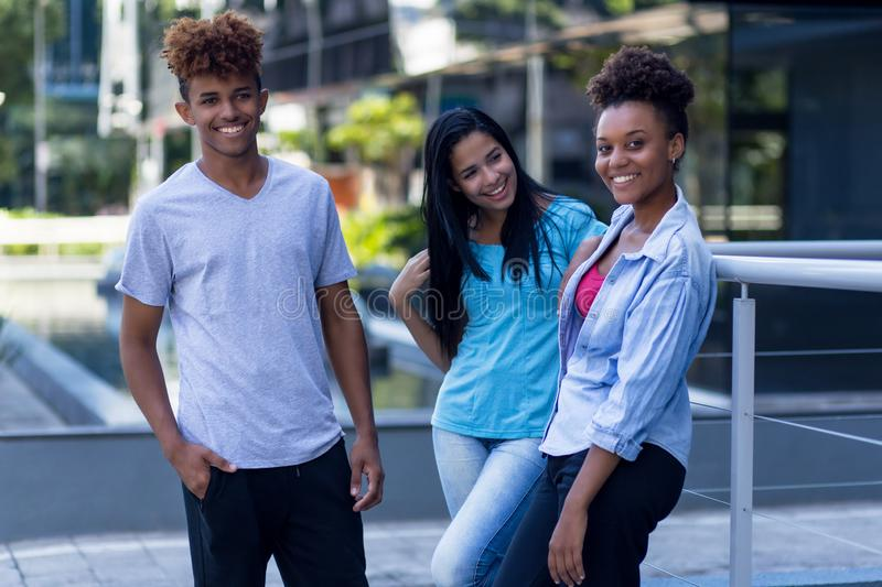 Young latin and hispanic and african american hipster people. Outdoors in city in summer stock photo