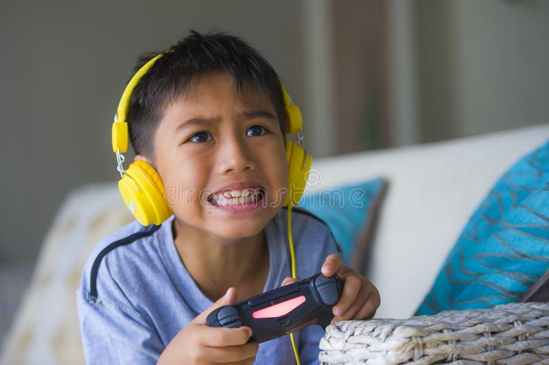 Young Latin little child excited and happy playing video game online with headphones holding controller having fun sitting on couc. Lifestyle portrait of young stock photos