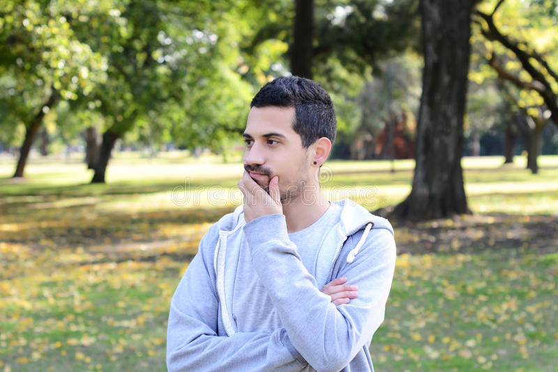 Young latin man thoughtful in a park. royalty free stock photo