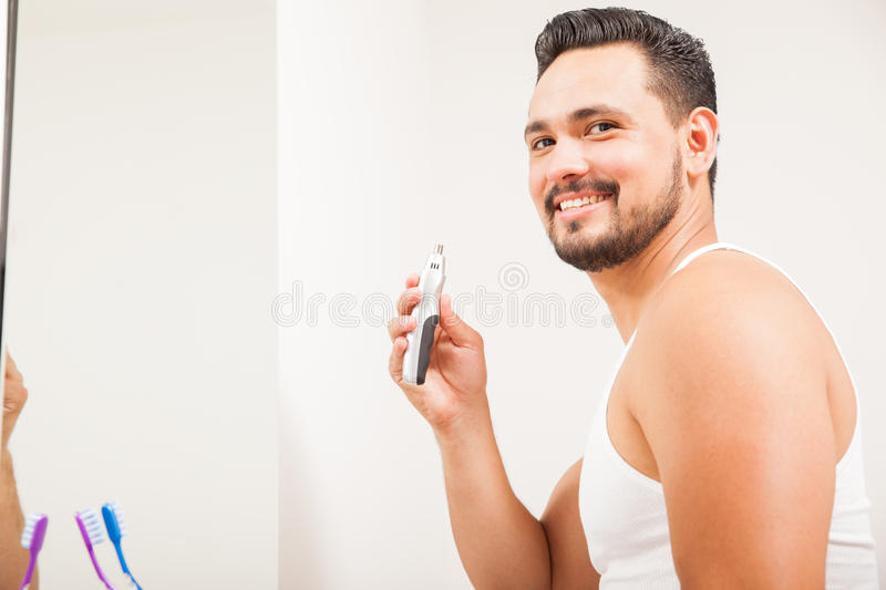 Young Latin man using a nose hair trimmer. Good looking young Latin man using a trimmer for nose hair and smiling in front of a bathroom mirror royalty free stock photos