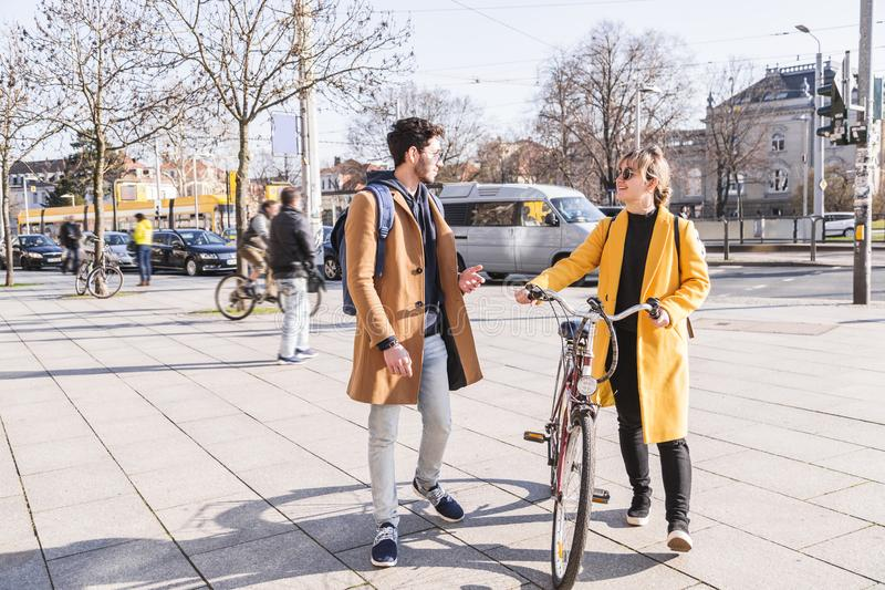 Young latin man walks near woman with bicycle royalty free stock photography