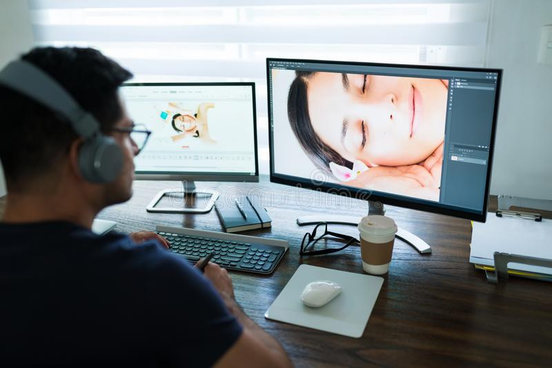 Male Freelance Editor Looking At Computer stock image