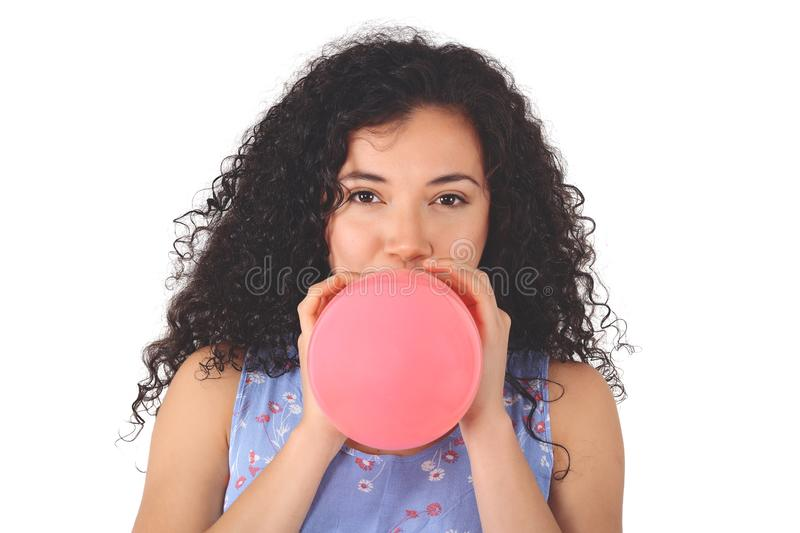 Young latin woman is blowing balloon stock photo