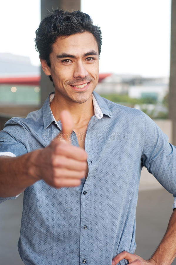 Young latino businessman holding thumbsup sign stock image