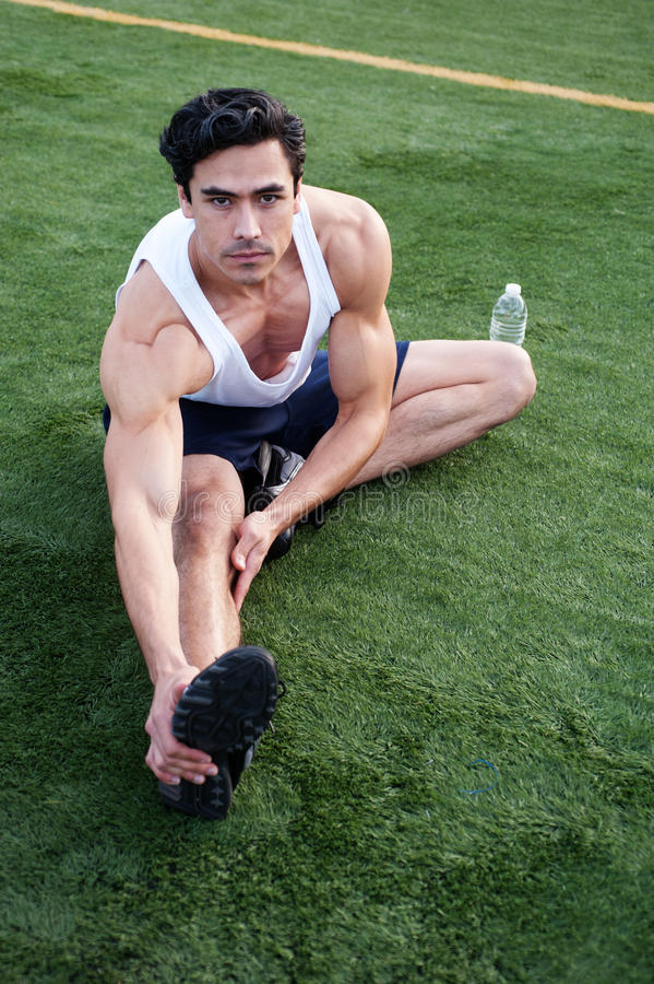 Young latino male athlete stretching stock image